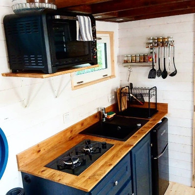 Amenagement sur-mesure de la cuisine (vue d'ensemble) de la tiny house Lecaninole du constructeur Baluchon.