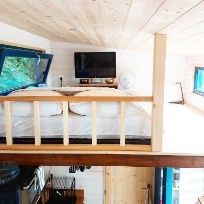 Amenagement sur-mesure de la chambre parentale en mezzanine de la tiny house Lecaninole du constructeur Baluchon.